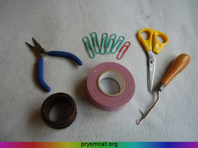 Clockwise from top left: round-nosed pliers (optional), large paperclips, scissors, latch-hook, hockey tape, napkin ring